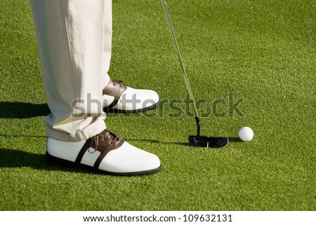 Low section of a man about to hit golf ball - stock photo