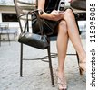 Low section of a sexy businesswoman sitting in a luxurious coffee shop terrace, using a cell phone. - stock photo
