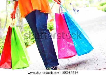 Low section of a woman holding multi colored shopping bags. Horizontal shot. - stock photo