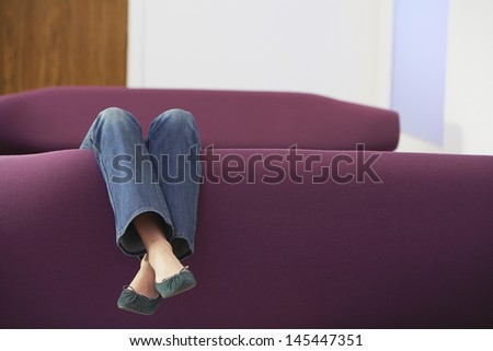 Low section of a woman relaxing upside down on sofa  - stock photo
