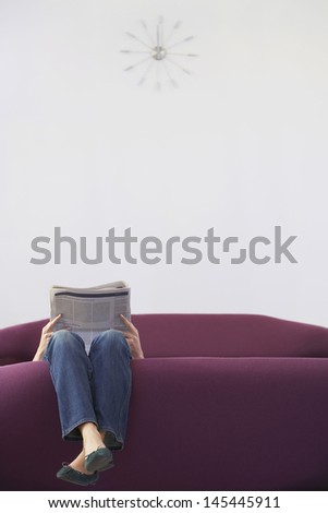 Low section of a woman relaxing upside down while reading newspaper on sofa  - stock photo