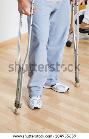 Low section of a woman standing with crutches on a wooden floor