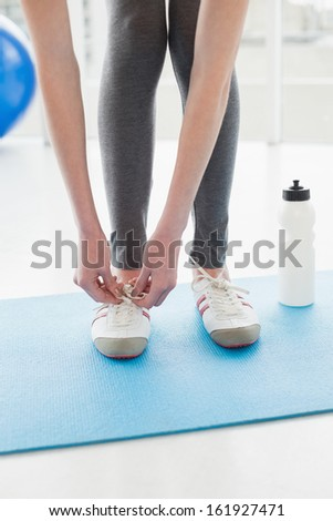 Low section of a woman tying shoes with water bottle on floor in fitness center