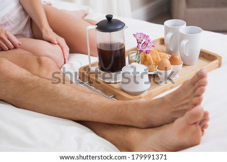 Low section of a young couple having breakfast in bed at home - stock photo