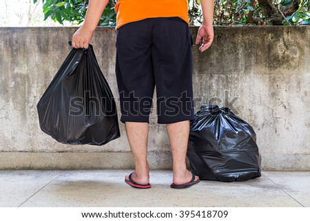 Low section of a young man carrying garbage bag - stock photo