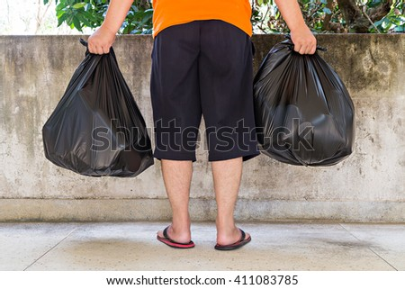 Low section of a young man carrying garbage bags - stock photo