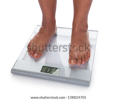 Low Section Of A Young On A Weighing Scale Against White Background - stock photo