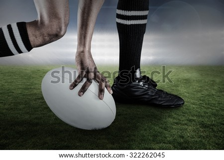 Low section of athlete holding ball while running against spotlights