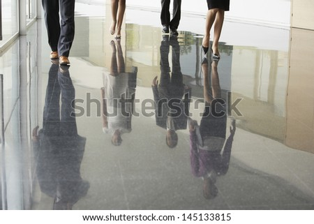 Low section of business people walking on marble flooring in office - stock photo