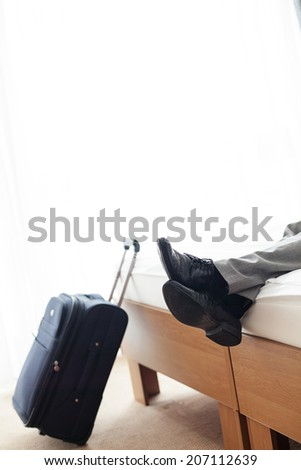 Low section of businessman lying on bed beside luggage in hotel room - stock photo