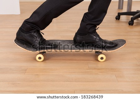 Low section of businessman on skateboard in office