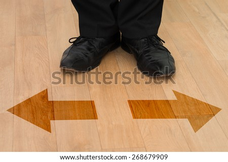 Low section of businessman standing in front of left or right arrows on floor