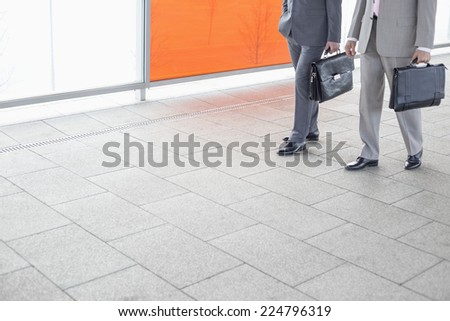 Low section of businessmen with briefcase walking in railroad station - stock photo