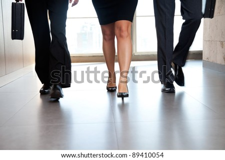 Low section of businesspeople walking along the office corridor - stock photo