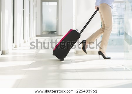 Low section of businesswoman with luggage exiting airport - stock photo