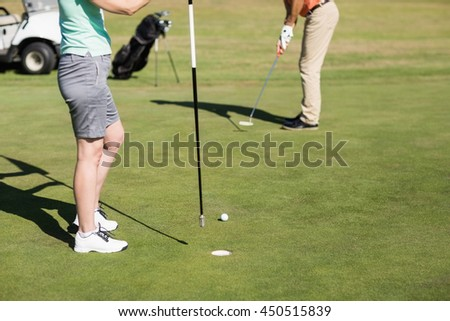 Low section of couple playing golf while standing on field