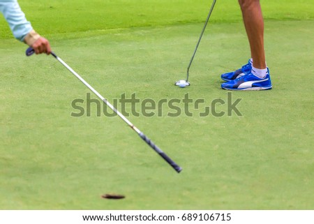 Low section of female golf player ready to hit the ball