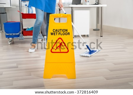 Low section of female janitor mopping floor by yellow wet caution sign in office