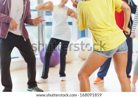 Low section of fitness class and instructor doing pilates exercise in bright room - stock photo
