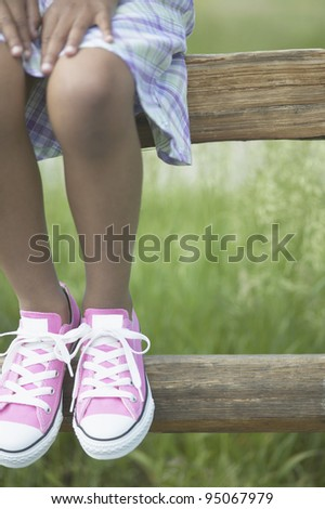 Low section of girl wearing pink shoes - stock photo