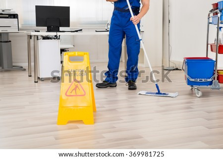 Low section of male janitor cleaning floor with mop in office - stock photo