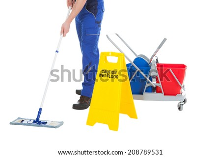 Low section of male servant mopping floor by Wet Floor Sign over white background - stock photo