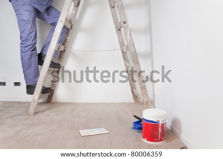 Low section of man's legs climbing wooden ladder