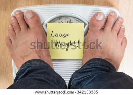 Low section of man standing on scale with loose weight sign - stock photo