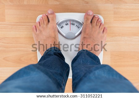 Low Section Of Man Standing On Weighing Scale - stock photo