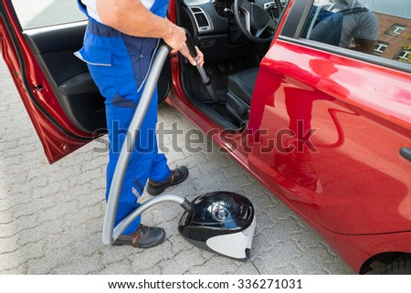 Low section of mature worker vacuuming car with vacuum cleaner