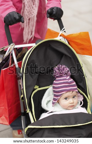 Low section of mother walking with baby in stroller - stock photo