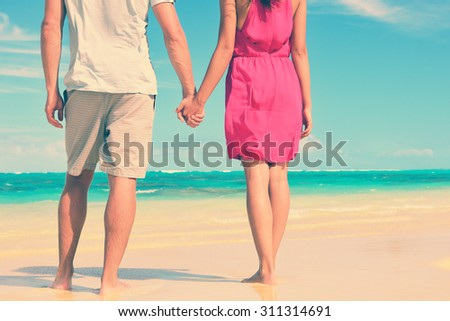 Low section of multiethnic couple holding hands on shore. Loving young tourists are standing at beach. They are spending leisure time together. - stock photo