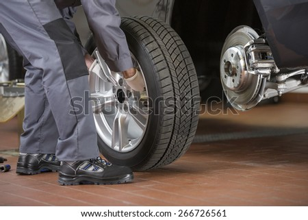 Low section of repairman fixing car's tire in repair shop - stock photo