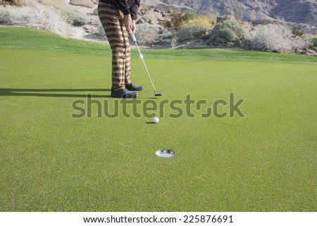 Low section of senior male golfer putting ball into hole at golf course - stock photo