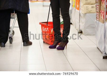 Low section of shoppers in shopping centre - stock photo