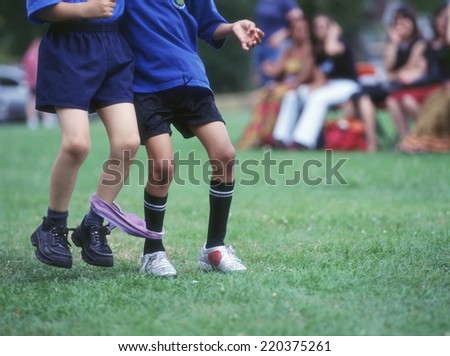 Low section of two boys in three-legged race - stock photo