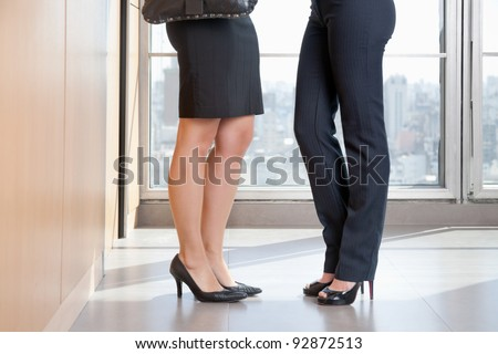 Low section of two female executives in high heels standing in office - stock photo