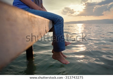 Low section of two people enjoying sunset while sitting on the pier with their feet above water - stock photo