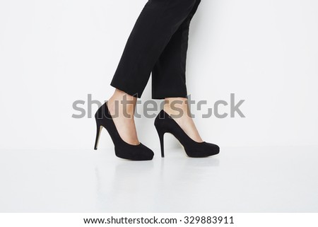 Low section of woman in black high heels