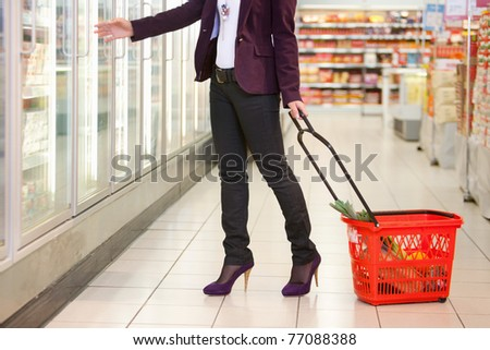 Low section of woman in front of refrigerator carrying basket in the supermarket - stock photo