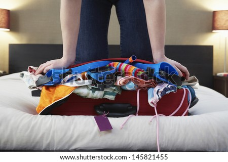 Low section of woman kneeling on overstuffed suitcase in bed - stock photo