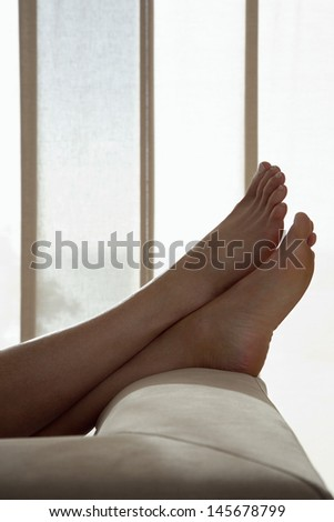 Low section of woman resting with feet up on sofa in living room - stock photo