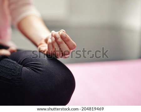 Low section of woman sitting cross-legged on mat meditating in yoga posture. Cropped image of woman practicing yoga with focus on hand. - stock photo