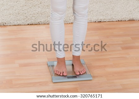 Low Section Of Woman Standing On Weighing Scale - stock photo