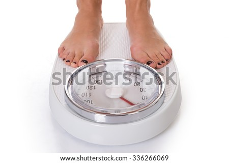 Low section of woman standing on weighing scale over white background - stock photo