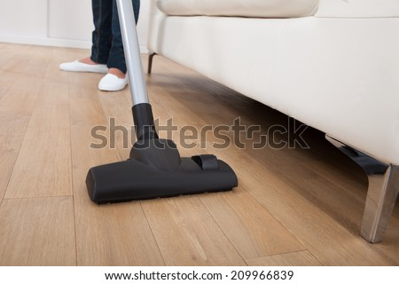 Low section of woman vacuuming hardwood floor at home - stock photo