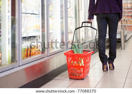 Low section of woman walking with basket near refrigerator in shopping centre