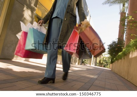 Low section of woman with shopping bags walking on pavement - stock photo