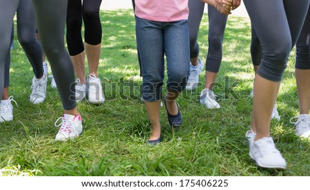 Low section of women and girl participating in breast cancer campaign in park - stock photo