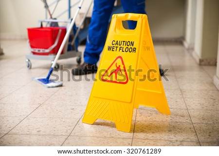 Low Section Of Worker Mopping Floor With Wet Floor Caution Sign On Floor - stock photo